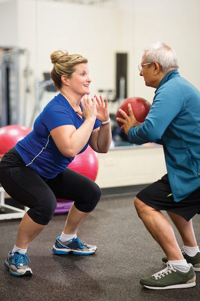 Woman instructing an older man with an exercise ball