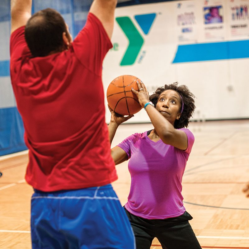 woman shooting a basketball with man guarding her