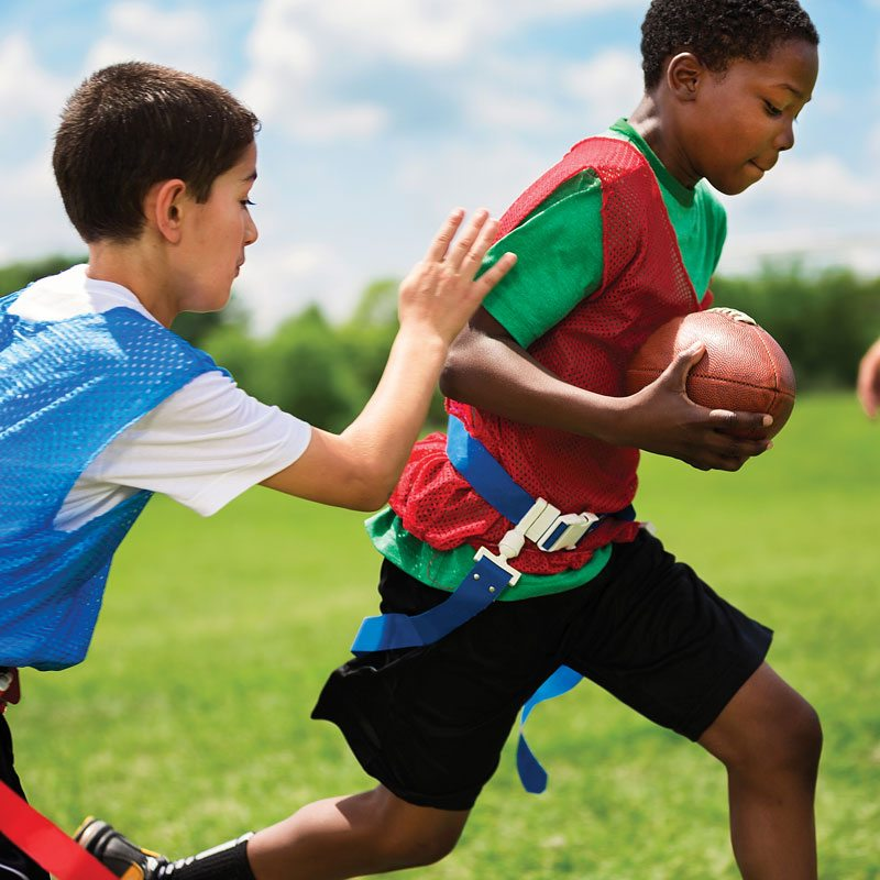 boys running playing flag football