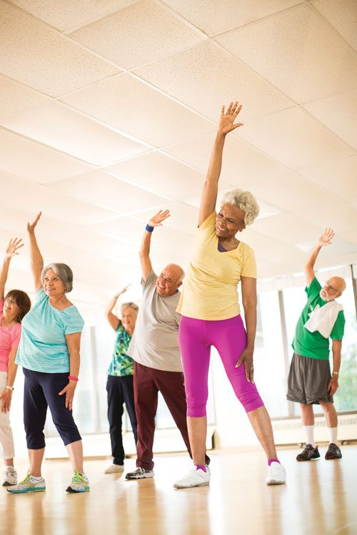 group of older adults stretching arms up