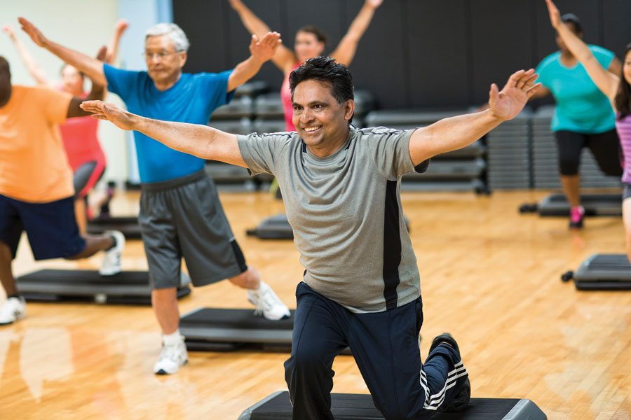 guy working out and smiling in a step aerobics class