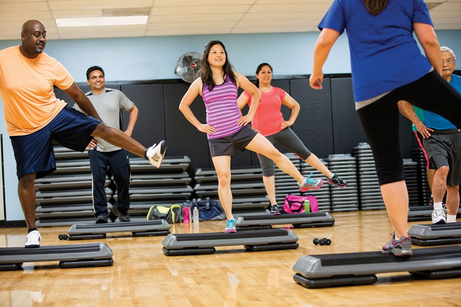 Step workout class with men and women