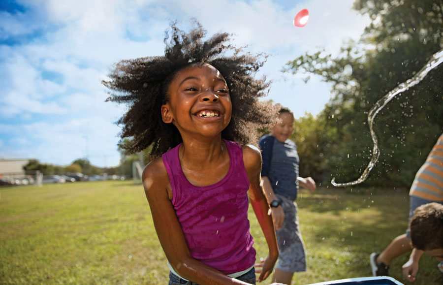girl smiling big while playing outside with water