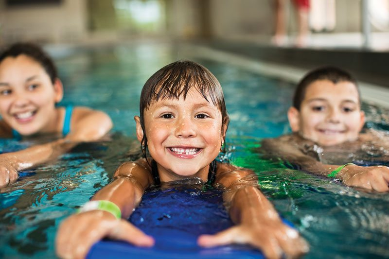 young girls and boy smiling in the Y pool for swimming lessons