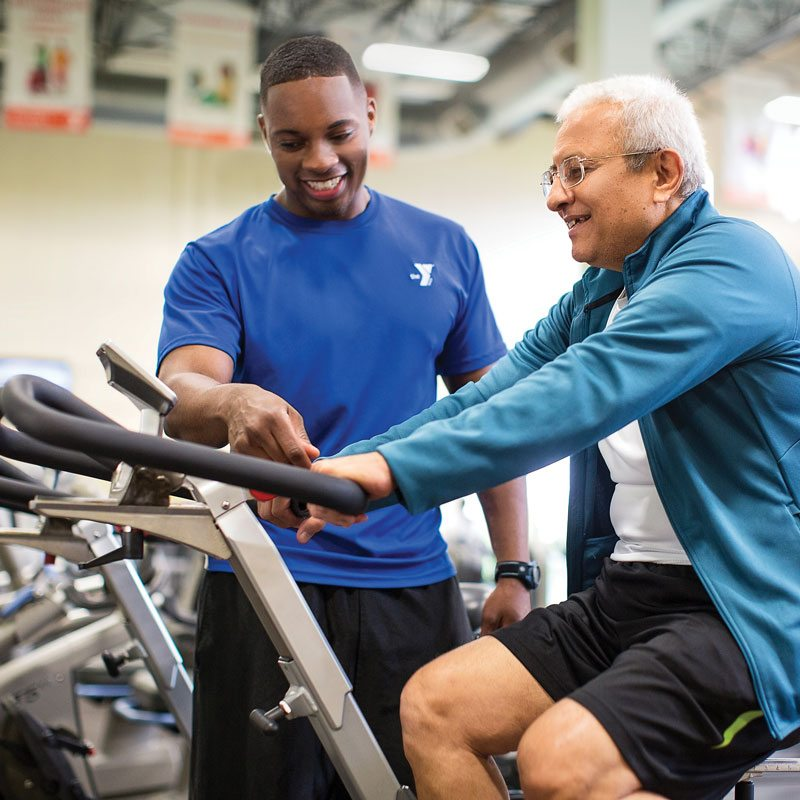 YMCA trainer helping older man on an exercise machine