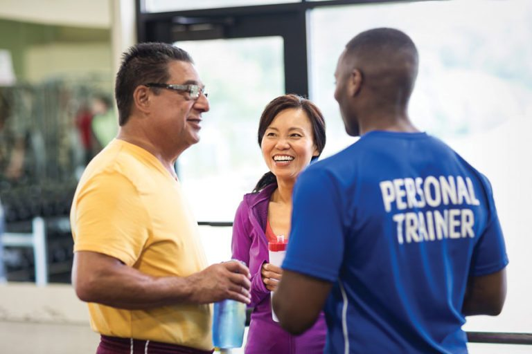 personal trainer talking with a woman and man in the gym