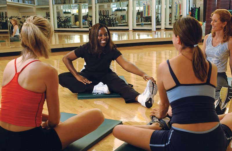 group of women stretching in a circle