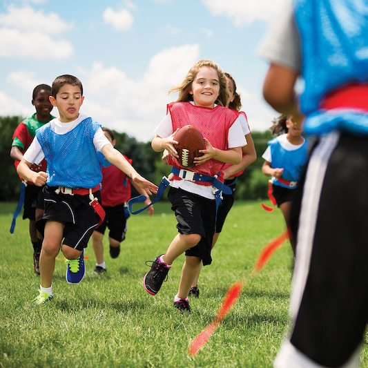 young girls and boys playing flag football