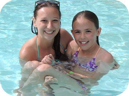 Older girl holding a younger girl in a pool