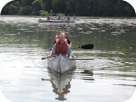 Two teen boys sitting in a canoe on the water