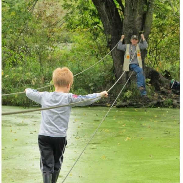 Young guide walking on a rope bridge across swampy water