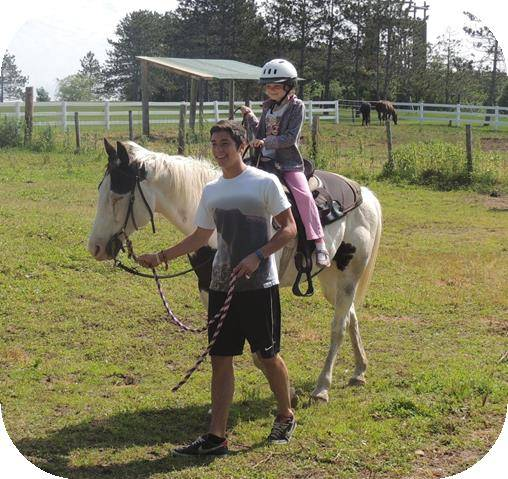 Young girl riding horse back with a teen boy leading the horse