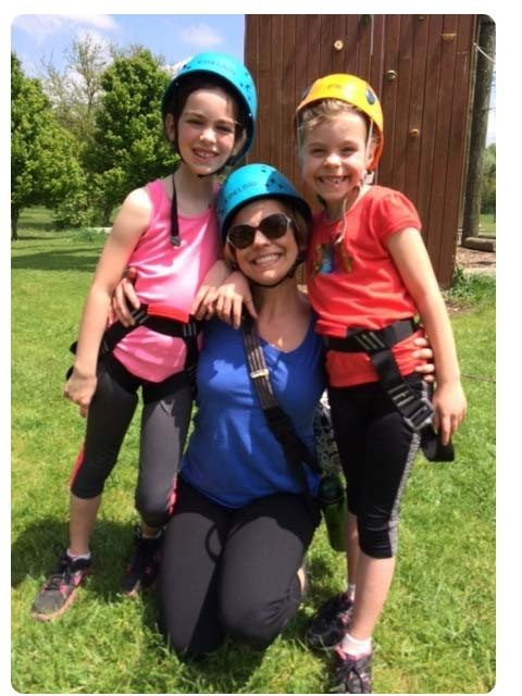 Mother and daughters smiling with climbing gear on