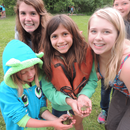 Group of girls holding toads and smiling