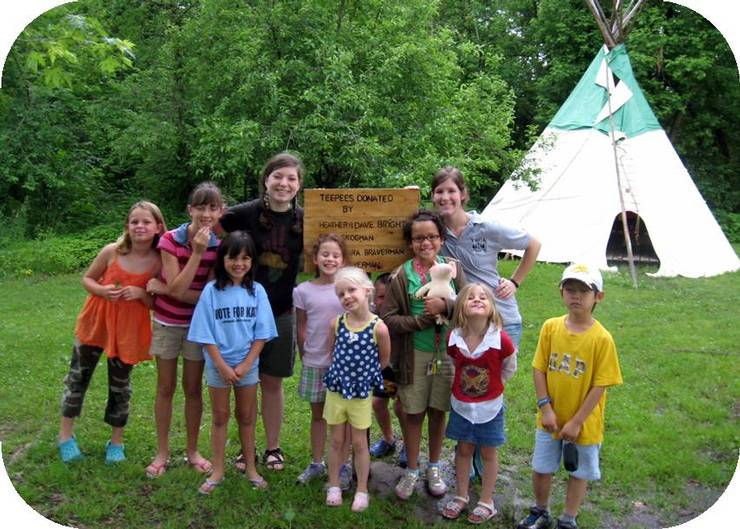 Group of young children in front of a teepee with camp leaders