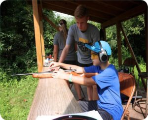 Young man helping a camper load a gun at a shooting range